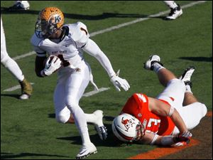 Kent State's Dri Archer escapes the clutches of BGSU defender Ted Oullett.