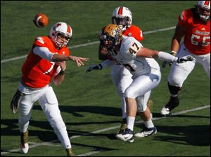 BGSU quarterback Matt Schilz passes as Kent State's Mark Fackler closes in.