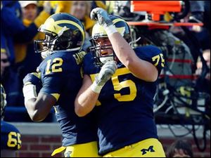 Michigan QB Devin Gardner (12) and Michael Schofield celebrate Gardner's touchdown run.