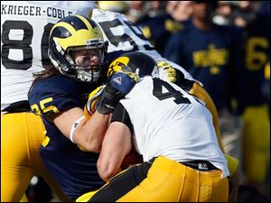 Michigan's DB Joe Bolden (35) tackles Iowa FB Mark Weisman.