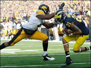 Michigan WR Roy Roundtree scores a touchdown against Iowa's DB Nico Law during the second quarter.