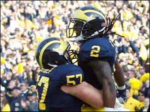 Michigan RB Vincent Smith (2) is hoisted by Elliott Mealer as the two celebrated Smith's touchdown run.