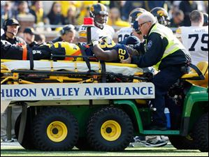 Michigan RB Fitzgerald Toussaint (28) is taken off the field in a stretcher after suffering a leg injury.