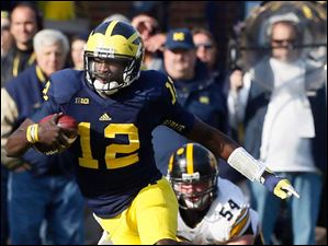 Michigan QB Devin Gardner (12) runs the ball against Iowa during the third quarter.