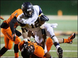 Whitmer's Tre Reditt-Sterrit, 12, runs over Massillon Washington's Brody Tonn.