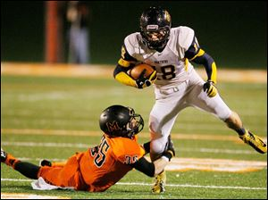 Whitmer's Nate Holley, 18, tries to elude Massillon Washington's Ryan Rambo during the first quarter.