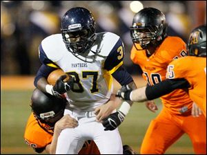 Whitmer's Jamal Bell, 37, is tackled by Massillon Washington's Devyn Nolen, 56, during the second quarter.