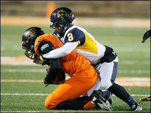 Whitmer High School player Matthew Sutter, 8, tackles Massillon Washington High School player Gareon Conley, 21.