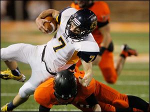Whitmer's Nick Holley, 7, is hit by Massillon Washington's Ryan Rambo, 35, after picking up a first down.
