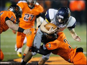 Whitmer quarterback Nick Holley, 7, is tackled by Massillon Washington High School players Rashaan Gray, 3, and Tylor Schneider, 19.