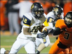 Whitmer High School player Tre Reditt-Sterrit, 12, runs past Massillon Washington player Ernie Baez for a touchdown.