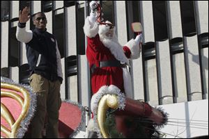 Co-grand marshall Olympic silver medalist and Toledo native Erik Kynard, left, and Santa Claus wrap up the 25th Anniversary Holiday Parade in Toledo, Ohio on November 17, 2012.
