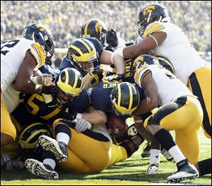 Michigan QB Devin Gardner (12) scores a touchdown against Iowa on a sneak during the first quarter Saturday, at Michigan Stadium in Ann Arbor, Michigan.