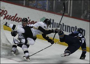 Wheeling's Cam Fergus and Peter Merth, 6,  collide with Walleye's Byron Froese during game.