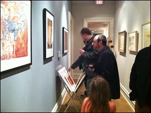 Luke Kende, of Memphis, Tenn., foreground, looks at some of the artwork done by his father, Ivan Kende, of Toledo, in the