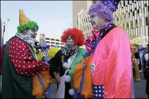 Jeff Gartz, left, Bill Carroll, and Nick Cron, members of the Distinguished Clown Corps, confer before the parade.