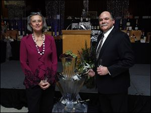 Dan Wakeman, president and CEO of ProMedica St. Luke's Hospital, and his wife Jasmine Wakeman admire an ice sculpture win display at the Mobile Meals 25th anniversary Wine Gala at Stranahan Great Hall.
