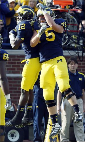 Michigan quarterback Devin Gardner, left, and Michael Schofield celebrate Gardner's touchdown run against Iowa during third quarter Saturday at Michigan Stadium in Ann Arbor. Gardner ran for three touchdowns and passed for three more in a victory.