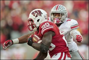 Ohio State's Ryan Shazier wraps up Wisconsin running back Montee Ball during the first half. Shazier had a team-high 12 tackles in the game.