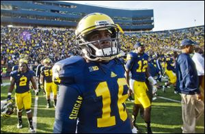 Michigan quarterback Denard Robinson walks off the field Saturday after the final home game of his career.