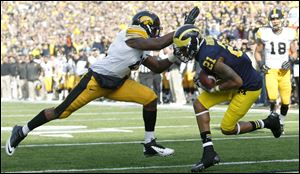 Michigan's Roy Roundtree gets behind Iowa's Nico Law for a second-quarter score.