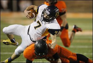 Whitmer quarterback Nick Holley is hit by Massillon Washington's  Ryan Rambo after picking up a first down.