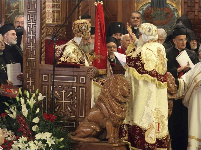 APTOPIX Mideast Egypt Pope Pope Tawadros II, 60, sits on the throne of St. Mark, the Coptic church's founding saint, wearing the papal crown, during an elaborate ceremony lasting nearly four hours, attended by the nation's Muslim prime minister and a host of Cabinet ministers and politicians, in the Coptic Cathedral in Cairo, Egypt.