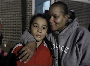 Nicholas M. Lopez, 9, and his mother, Markeda Holcomb-Brownlee, mourn the loss of murder victim CreJonnia Bell, 19, during her vigil at her mother's apartment at the Moody Manor in Toledo. Bell was Nicholas' sister and KeeKee's daughter.