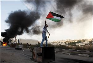 A Palestinian waves the national flag during a protest against Israel's airstrikes in Gaza.