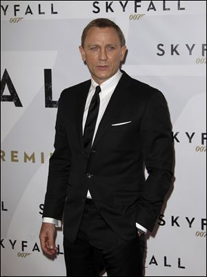 Actor Daniel Craig poses for photos as he arrives for the premier of the latest James Bond film,