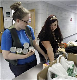 Christina Perry, 24, left, and Stacey Field, right, help stock canned goods and non-perishable food collected during the