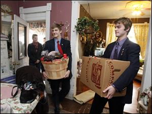 Laurie Yeager, left, her son Peter Yeager, center, and Marc Elfering, right, deliver Thanksgiving food baskets to Angie Graves and her family.