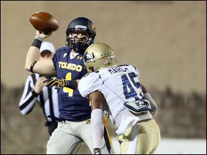 Toledo QB Austin Dantin throws the ball against Akron defender Justin March.
