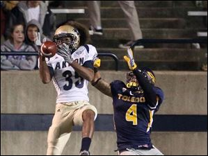 Akron's Keith Sconiers scores a touchdown as Toledo's Jordan Haden fails to break up the pass.