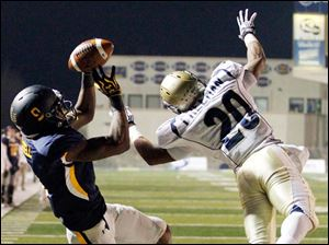 Akron corner back Malachi Freeman dives in an attempt to break up a pass intended for Toledo's Alonzo Russell.