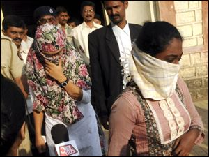 Face covered Shaheen Dhada, left, and Renu Srinivas, Indian women arrested for their Facebook posts, come out of a court in Mumbai, India, today.