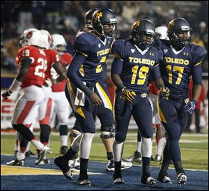 University of Toledo RB Cassius McDowell (19) celebrates scoring a touchdown with Terrance Owens (2) and Dwight Malcolm (17)  against Ball State Tuesday, 11/06/12, at the Glass Bowl in Toledo.
