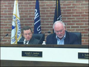 Council president Joseph Lawless, right, reads minutes from the recreation committee at Tuesday's city council meeting as clerk David Creps looks on.