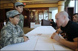 Lukas Nieto, 4, and his brother Zeke Kniffen, 10, get autographs from mixed martial arts fighters including 2004 Olym­pian Devin Var­gas, a Start High School grad­u­ate who is now a pro­fes­sional boxer.