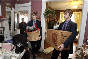 Laurie Yeager, in doorway, her son Peter Yeager, and Marc Elfering carry food into the East Toledo home of Angie Graves and her family. St. Francis students delivered about 50 baskets on Tuesday to area families. The baskets are expected to feed nearly 300 people over the holiday.