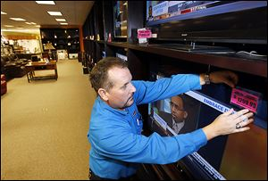 Jeff Podgorski tags televisions at Appliance Center in Maumee in preparation for Black Friday. The store will be closed today.