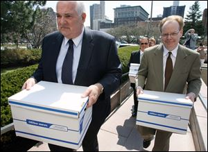 Andy Stuart, right, and Tom Schlachter carry boxes of petitions into Government Center in 2009 as part of an effort to recall then-Mayor Carty Finkbeiner.