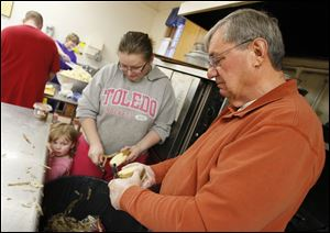 Dave Luce, right, and Lisa Hall, with daughter Baileigh Hall, 2,  peel potatoes at Pilgrim Church in Toledo in preparation for a Thanksgiving dinner that expects to feed upward of 400 people.
