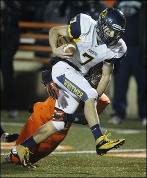 Whitmer quarterback Nick Holley breaks a tackle against Massillon Washington. He has rushed for 1,734 yards and passed for 1,587 yards in leading the Panthers to the Division I state semifinals.