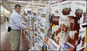 Randy Whitehead, manager at the Andersons General Store in Maumee, straightens a display. The chain plans to offer discounts on total purchases.