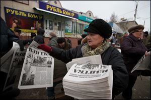 A woman hands out copies of  Eduard Mochalov's newspaper Bribe in Cheboksary, the capital city of Chuvashia, Russia.