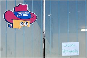 A 'closed permanently' sign joins a Twinkie The Kid poster on the Wonder Hostess Bakery Outlet store in Victorville, Calif. The store closed Saturday.