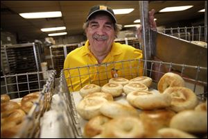 Barry Greenblatt, 63, owner of Barry Bagels, offers his signature smile over an assortment of bagels at his  Sylvania store. Mr. Greenblatt has been making bagels since 1972.