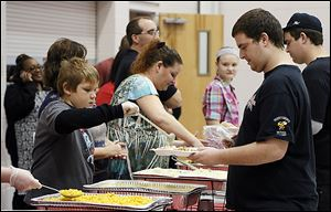 Volunteer Noah Power, 11, serves food to Ryan Kinnison of Northwood during a Thanksgiving dinner sponsored by House of Bread Ministries Inc. at  Bethlehem Baptist New Life Center.