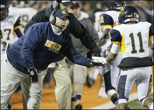 Whitmer coach Jerry Bell congratulates Me'Gail Frisch for scoring a touchdown against Massillon Washington. Bell has guided the Panthers to an unbeaten season in his first season as head coach.